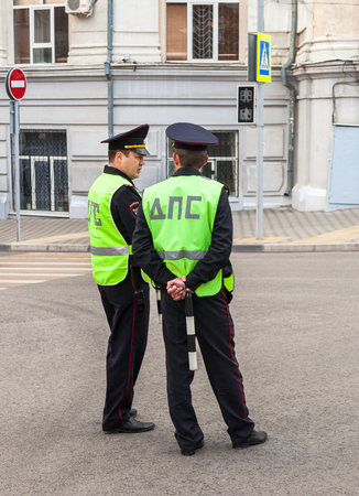 regulate: SAMARA, RUSSIA - SEPTEMBER 11, 2016: Russian police patrol officers of the State Automobile Inspectorate regulate traffic on city street