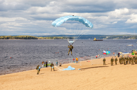 parachutists: SAMARA, RUSSIA - SEPTEMBER 11, 2016: Military parachutists jumper on a  wing parachute execute a controlled descent by parachute on a beach