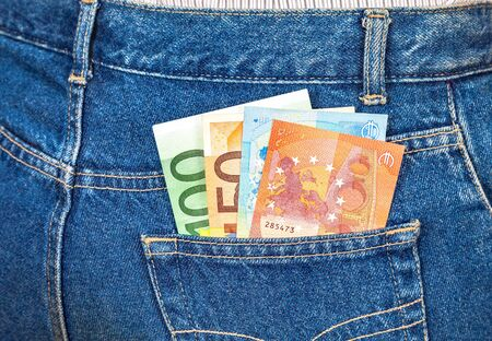 money in the pocket: Euro banknotes sticking out of the blue jeans pocket. Money for travel and shopping Foto de archivo
