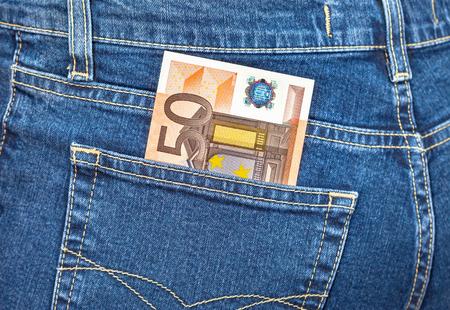 money in the pocket: Billete de banco de ? 50 que sobresale del bolsillo de los tejanos. El dinero para viajes y compras