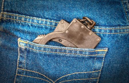 culprit: Black metal handcuffs in back jeans pocket Stock Photo