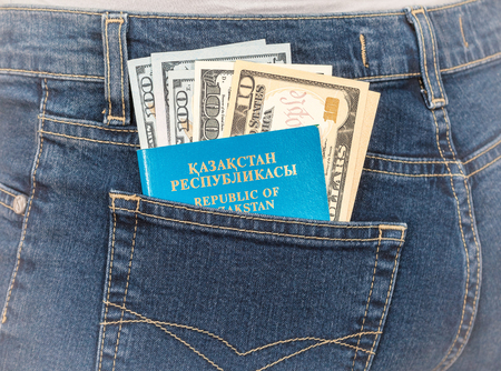 money in the pocket: Kazakhstan passport and dollar bills in the back jeans pocket. Money for travel and shopping Foto de archivo