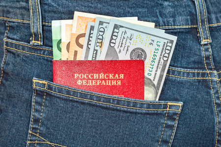 bolsa dinero: Russian passport, euro and dollar bills in the back jeans pocket. Money for travel and shopping Foto de archivo
