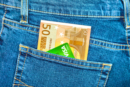 MOSCOW, RUSSIA - NOVEMBER 27, 2016: Banknote 50 euro and credit card Visa in back jeans pocket