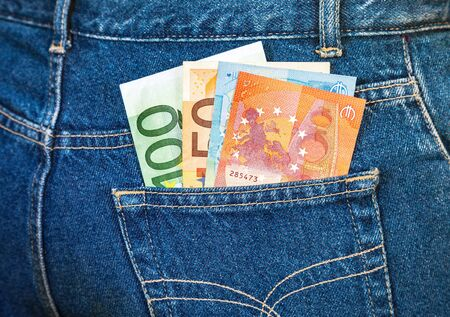 bolsa dinero: Euro banknotes sticking out of the blue jeans pocket. Money for travel and shopping Foto de archivo