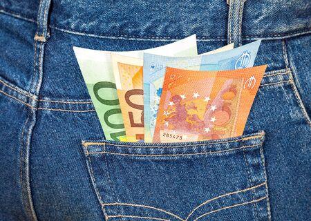 money in the pocket: Los billetes en euros que salen de la bolsillo de los tejanos. El dinero para viajes y compras Foto de archivo
