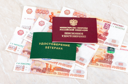 oldage: MOSCOW, RUSSIA - DECEMBER 18, 2016: Russian Pension Certificate and Veteran Certificate lying over banknotes. Inscription on Certificate in russian: Russian Ministry of Defense, Pension Certificate, Veteran Certificate
