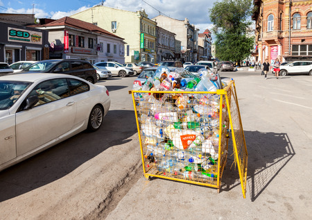 crushed cans: SAMARA, RUSSIA - SEPTEMBER 10, 2016: The container for collecting plastic bottles of various drinks for recycling on the city street in summer sunny day