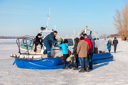 hovercraft: SAMARA, RUSSIA - MARCH 11, 2017: Embarkation people on the passenger hovercraft Hivus-4 at the ice of the frozen Volga river in Samara, Russia