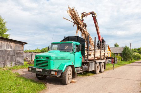 Novgorod region, Russia - july 25, 2016: Log hydraulic manipulator unloaded timber from the truck in summer day