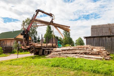 Novgorod region, Russia - july 25, 2016: Log hydraulic manipulator unloaded timber from the truck in summer day
