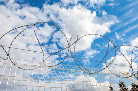 Barbed wire against the blue sky background. Protective fencing specially protected object of barbed wire Stock Photo