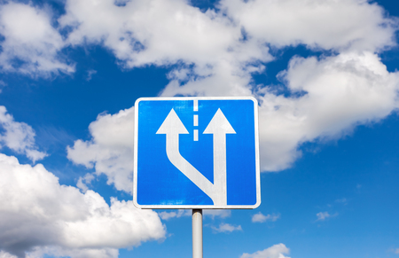 post: Road sign against the blue sky with clouds Stock Photo