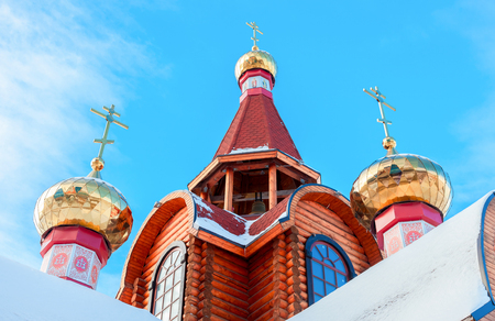 yule log: Domes with crosses on wooden orthodox church against the blue sky in Samara, Russia