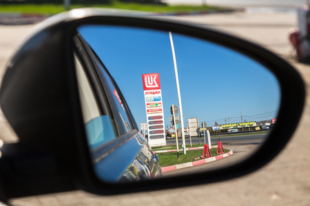 trademark: Samara, Russia - April 30, 2017: Gas station Lukoil price sign reflection in the rearview mirror of a car Editorial