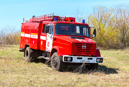Samara, Russia - April 30, 2017: Red fire truck EMERCOM of Russia parked up on the spring field Editorial