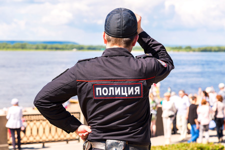 Samara, Russia - May 12, 2017: Unidentified Russian police officer in uniform at the embankment of Volga river. Text in russian: Police Editorial