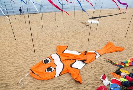 Samara, Russia - May 12, 2017: An air kite in the form of a big orange fish lies on a sandy beach