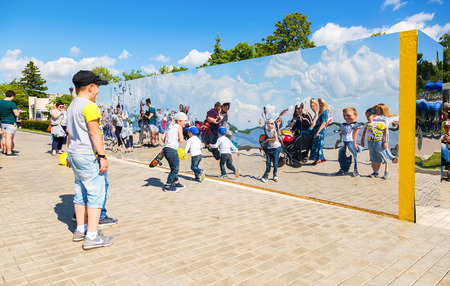 Samara, Russia - May 12, 2017: People near the giant stainless steel mirror at the city park in summer sunny day