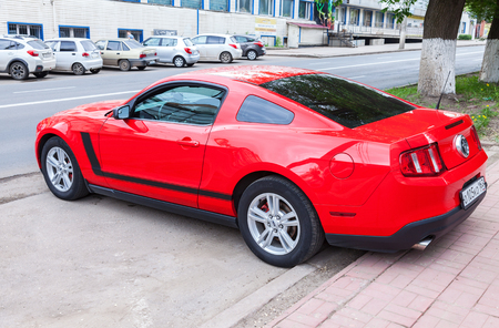 Samara, Russia - May 22, 2017: Red Ford Mustang parked up at the city street in summer day. The Ford Mustang is an American automobile manufactured by Ford