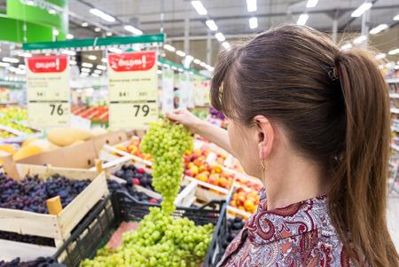 Samara, Russia - September 3, 2017: Young woman choosing fresh grapes at shopping in supermarket