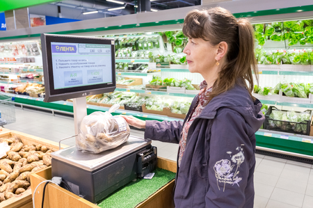 Samara, Russia - September 5, 2017: Young woman weighing potatoes on electronic scales in produce department of the supermarket