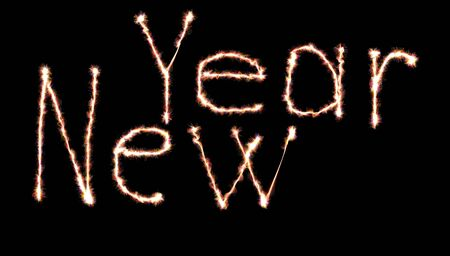 Glowing neon Happy new year lettering written with fire flame or smoke over black background