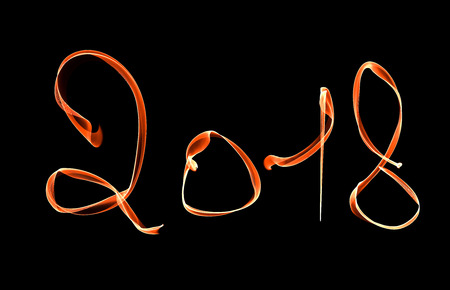 Glowing neon Happy new year 2018 lettering written with fire flame or smoke over black background