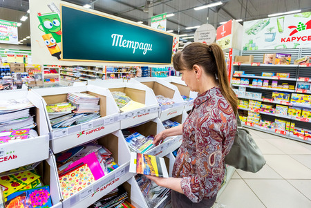 Samara, Russia - September 3, 2017: Woman choosing office supplies at shopping in superstore Karusel. Text in Russian: Writing-books 新聞圖片