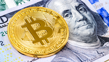 Golden bitcoin lying over one hundred american dollars bill close up. Business concept