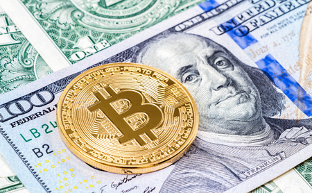 Golden bitcoin lying on the one hundred american dollar. Business concept of worldwide cryptocurrency Stock Photo
