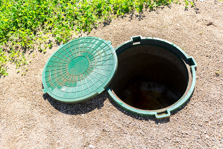 Opened unsecured sewer manhole of rural septic tank with green plastic cover