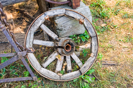 Old wooden broken wheel in the abandoned village in summer day Stock Photo
