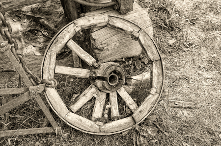 Retro photo with old wooden broken wheel in the abandoned village