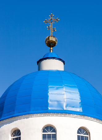 Dome of Russian orthodox church with golden cross against the blue sky 스톡 콘텐츠