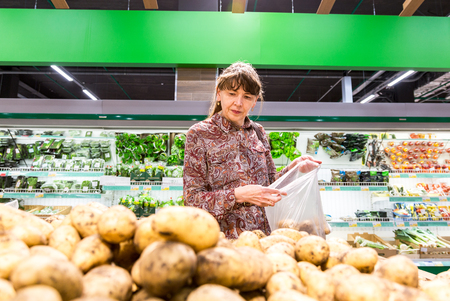 Samara, Russia - September 16, 2017: Young woman choosing fresh potatoes at shopping in chain hypermarket