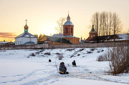 Borovichi, Russia - April 10, 2016: Fishermen in winter fishing near the walls of the Holy Spirit Monastery Editorial