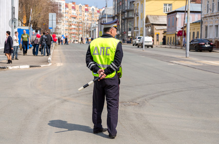 Samara, Russia - May 1, 2018: Russian police officer of the State Automobile Inspectorate regulate traffic on city street