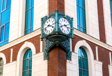 Vintage street clock hanging on a corner of brick building in Samara, Russia Stock Photo
