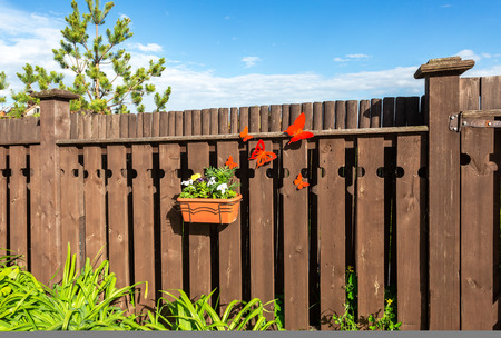 Flower pot with decorative flowers hanging on the wooden fence in village