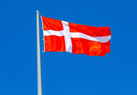 Flag of Denmark waving in the wind against the blue sky Stock Photo