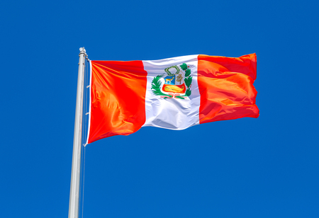 Flag of Peru waving in the wind against the blue sky