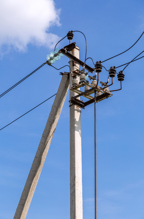 High voltage electricity pylon with wires against the blue sky