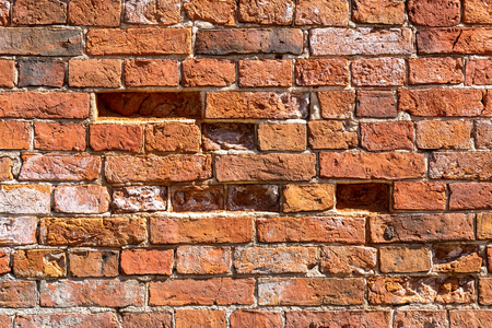 Grunge weathered red brick wall as background texture. Bricks masonry with uneven seams Stock Photo
