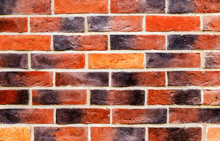 Weathered red brick wall as background texture. Bricks masonry with uneven seams