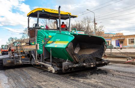 サマラ、ロシア - 4月29、2018:街の通りにアスファルトの表面を敷設する作業。アスファルトの輸送および敷設のための機械 報道画像