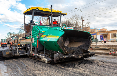 Samara, Russia - April 29, 2018: Work on laying the asphalt surface on a city street. Machines for transportation and laying of asphalt Editorial
