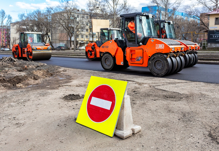 Samara, Russia - April 29, 2018: Road sign Stop against the background of laying the asphalt on a city street