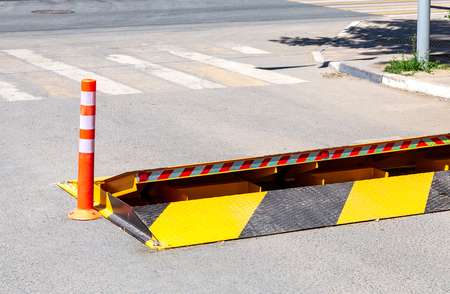 Road barrier with yellow and black striped caution pattern, road fence construction at the city street