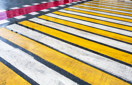 Pedestrian crossing with white, yellow and red stripes on wet asphalt Stock Photo